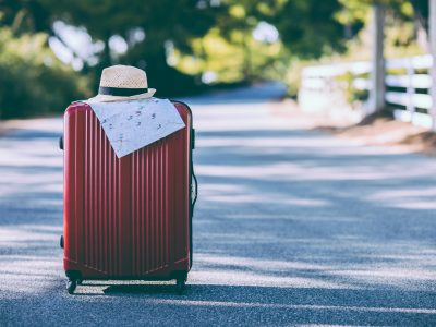 Red suitcase, hat and map on the road in countryside. Summer vacation and travel concept