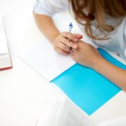 girl with book writing to notebook at school